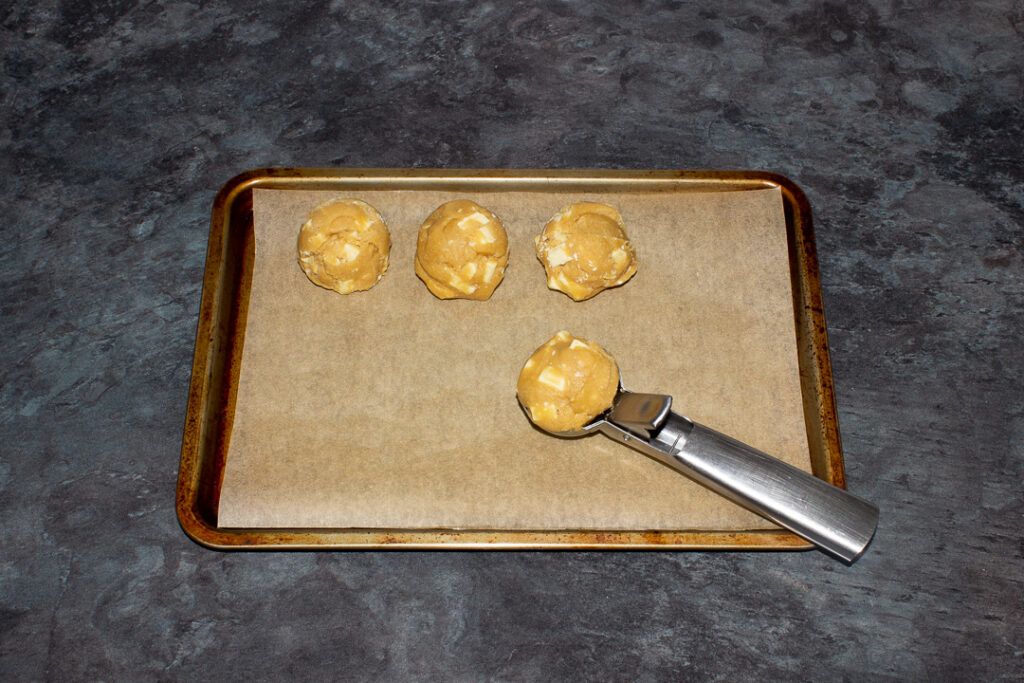 Balls of white chocolate chip cookie dough on a lined baking tray with an ice cream scoop