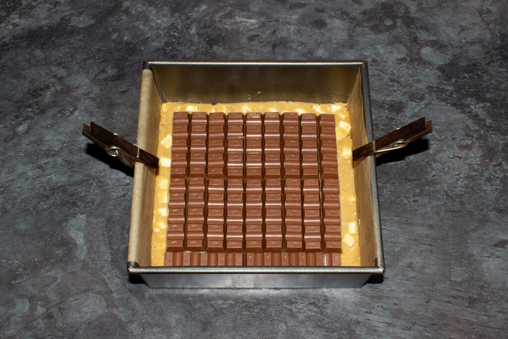White chocolate chip cookie dough pressed into the bottom of a lined square baking tin, topped with lots of Kinder bars.