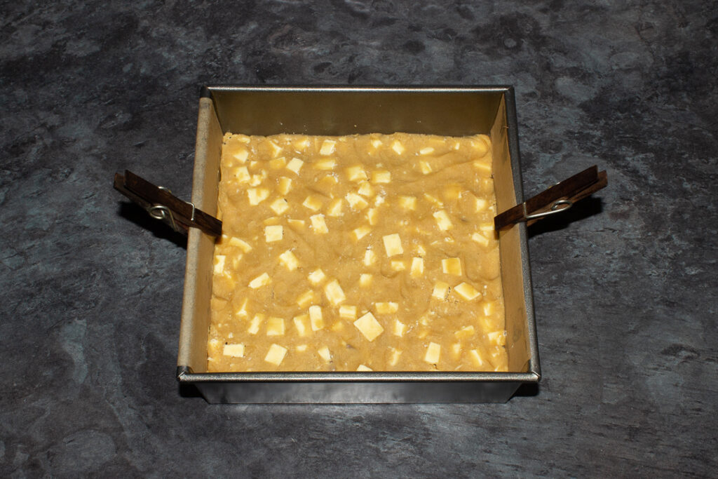 A lined square baking tin filled with 2 layers of white chocolate cookie dough and Kinder bars.