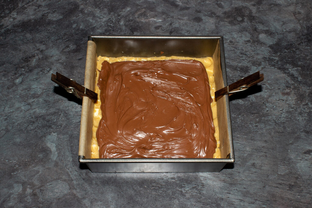 A lined square baking tin filled with 2 layers of white chocolate cookie dough, a layer of Kinder bars and a layer of Nutella spread.