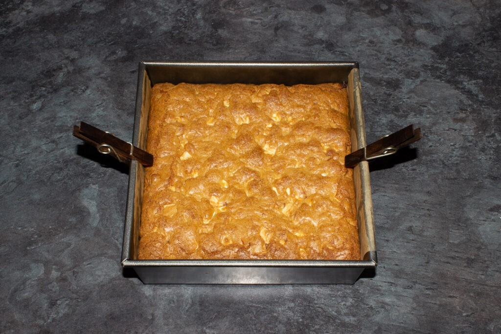 Baked white chocolate kinder nutella cookie bars cooling in a lined square baking tin