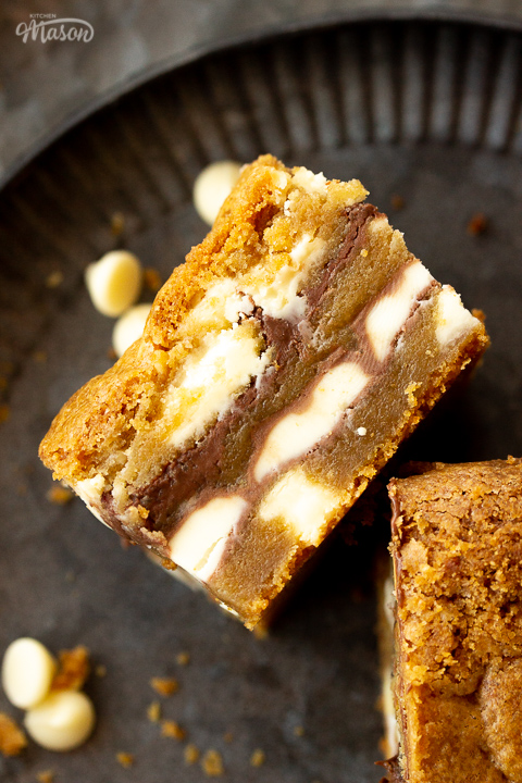 Close up of a white chocolate kinder nutella cookie bar on it's side on an iron plate. There are white chocolate chips and cookie crumbs scattered around it.