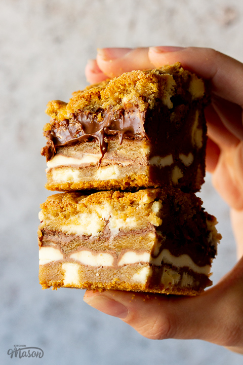 2 white chocolate kinder nutella cookie bars being held in a stack by a hand against a cream backdrop