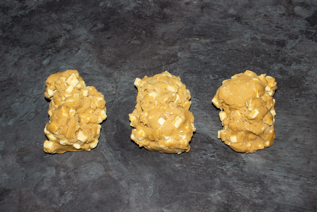 White chocolate chip cookie dough divided into 3 pieces on a kitchen worktop