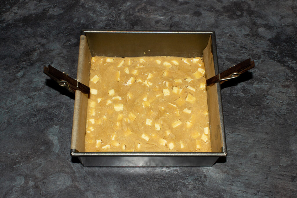 White chocolate chip cookie dough pressed into the bottom of a lined square baking tin.