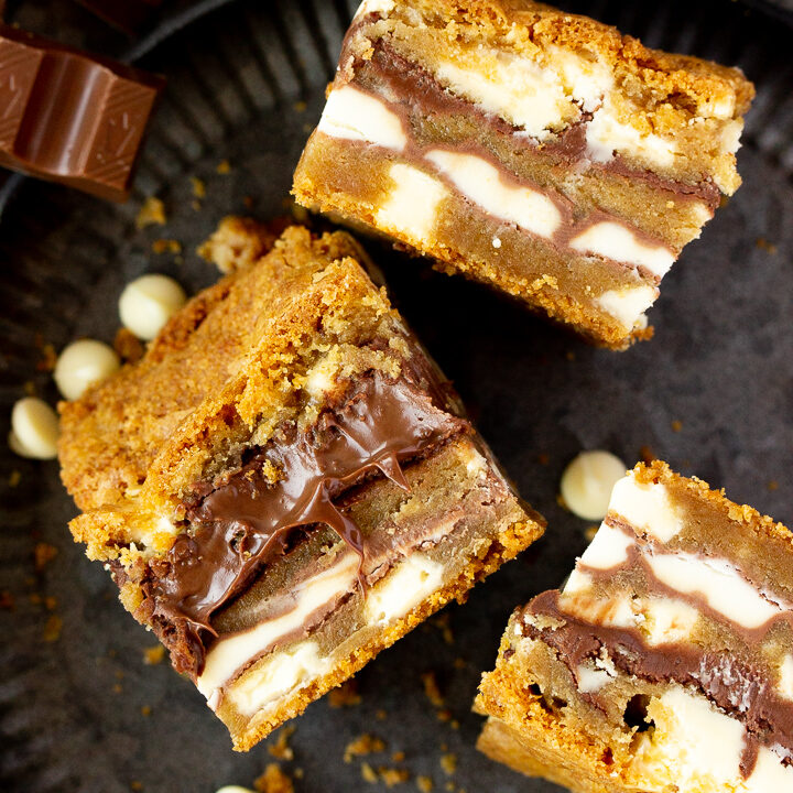 Close up of 3 white chocolate kinder nutella cookie bars on their sides set on an iron plate with white chocolate chips, kinder bars and cookie crumbs scattered around it.