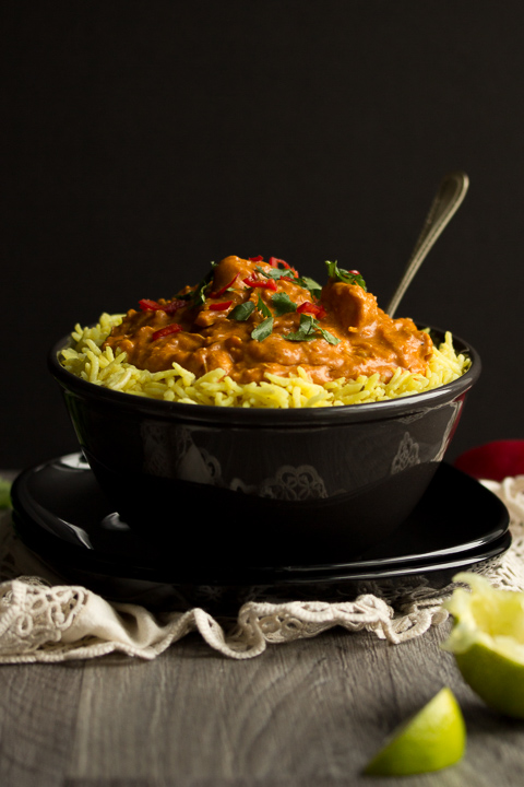 A side view shot of a black bowl filled with chicken curry over rice, topped with coriander and red chilli with a fork inside. There's a cream napkin and lime wedges in the background.