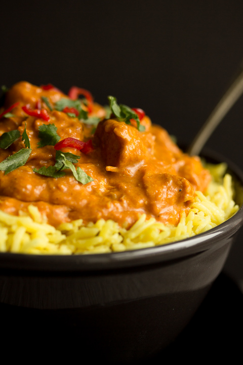 Close up of a black bowl filled with chicken curry over rice, topped with coriander and red chilli with a fork inside.