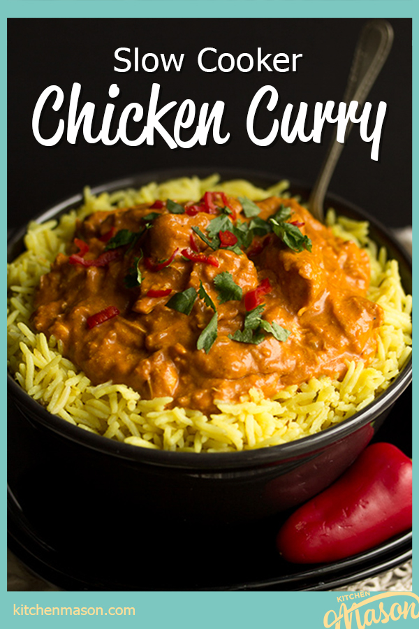A black bowl filled with chicken curry over rice, topped with coriander and red chilli with a fork inside. Set on a black plate over a cream napkin with a whole red chilli in the background..