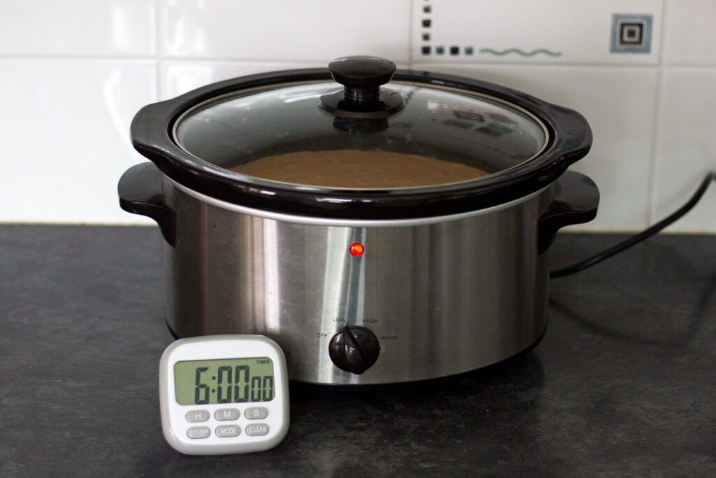 Slow cooker chicken curry in a slow cooker with a timer on display in front.