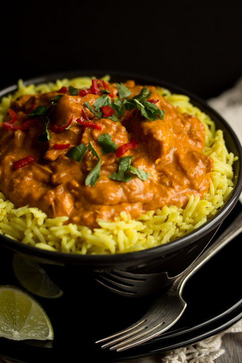 A black bowl filled with chicken curry over rice, topped with coriander and red chilli. There's a black plate underneath with a fork on it plus a lime wegde and a cream linen napkin in the background.