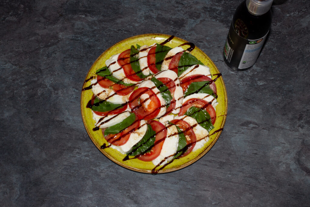 Slices of tomato, basil and mozzarella in a layered circle on a green plate with olive oil, balsamic vinegar and a balsamic glaze drizzled over the top.