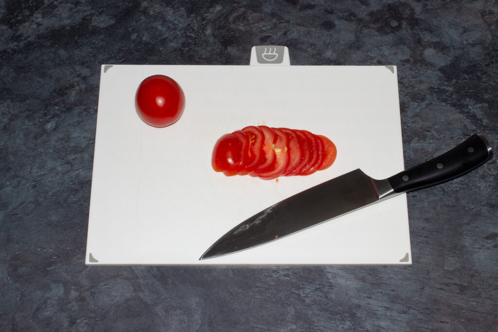 a Tomato being thinly sliced with a sharp knife on a chopping board.