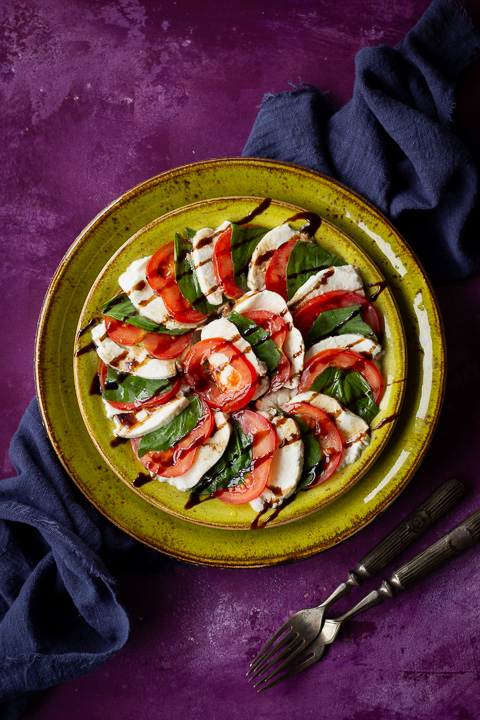 2 stacked green plates with a caprese salad drizzled with a balsamic glaze on top. Set on a purple backdrop there's also a blue linen napkin and 2 forks in the background.