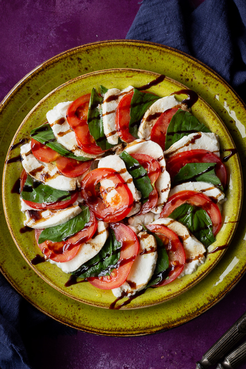 Close up of 2 stacked green plates with a caprese salad drizzled with a balsamic glaze on top. Set on a purple backdrop there's also a blue linen napkin and 2 forks in the background.