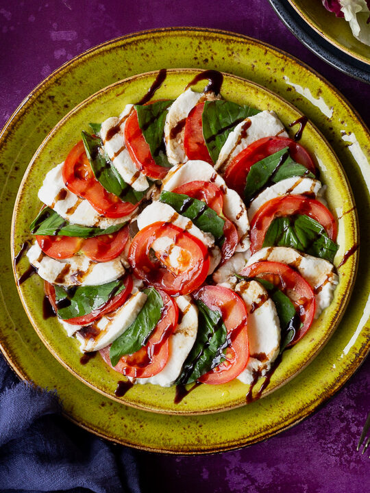2 stacked green plates with a caprese salad drizzled with a balsamic glaze on top. Set on a purple backdrop, there is a bowl of lettuce, a plate of sliced beetroot, a blue linen napkin, 3 whole tomatoes and 2 forks in the background.