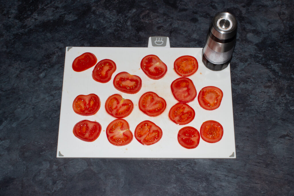 Tomato slices being sprinkled with salt on a white chopping board.