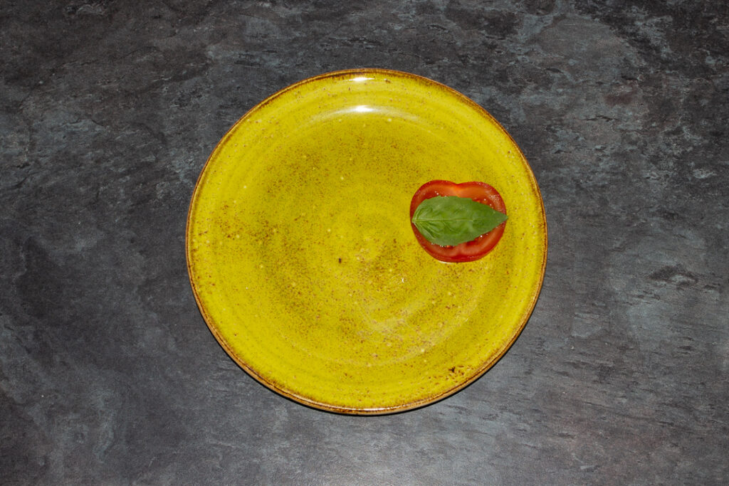 A slice of tomato topped with a basil leaf on a green plate.