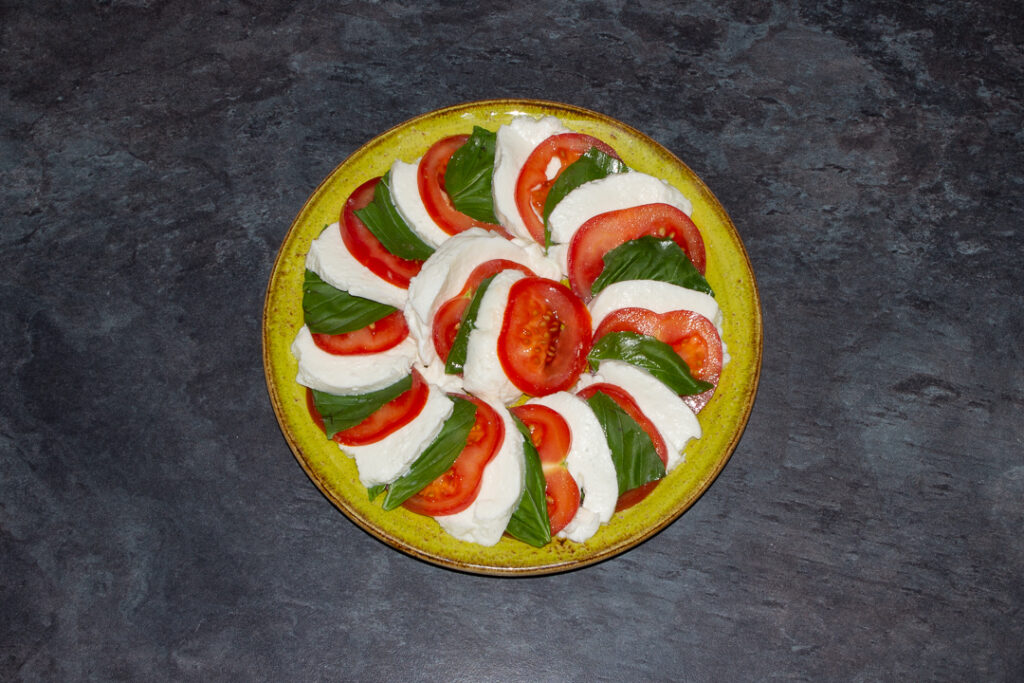Slices of tomato, basil and mozzarella in a layered circle on a green plate.