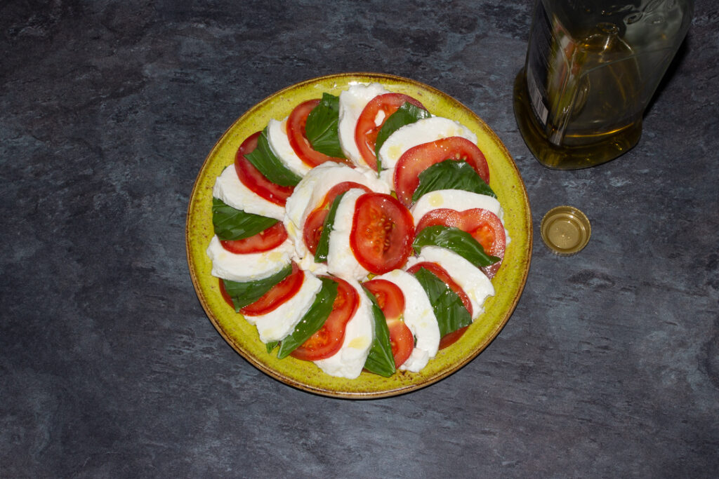 Slices of tomato, basil and mozzarella in a layered circle on a green plate with olive oil drizzled over the top.