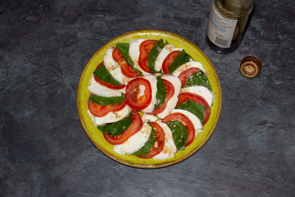 Slices of tomato, basil and mozzarella in a layered circle on a green plate with olive oil and balsamic vinegar drizzled over the top.