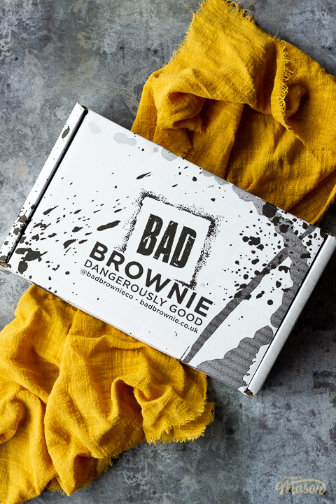 A closed box of Bad Brownie brownies on a yellow linen napkin against a grey backdrop.
