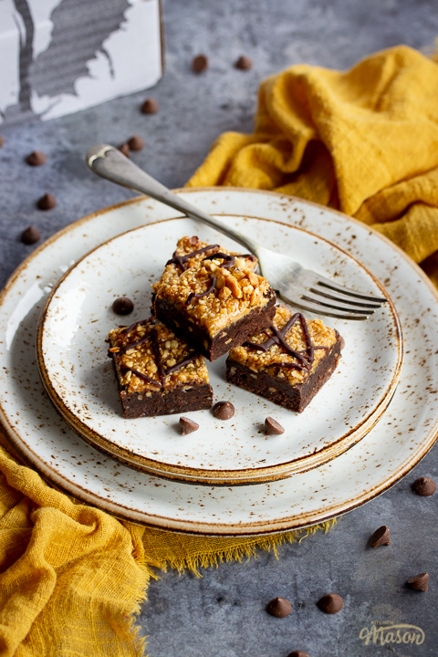 4 peanut butter brownies in a stack on top of 3 stacked plates with a fork. Set on a yellow linen napkin over a grey background, there's also scattered chocolate chips and a Bad Brownie box in the background.