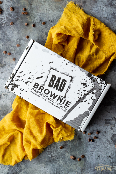 A closed box of Bad Brownie brownies on a yellow linen napkin against a grey backdrop with chocolate chips scattered around.