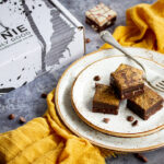 4 salted caramel brownies in a stack on top of 3 stacked plates with a fork. Set on a yellow linen napkin over a grey background, there's also scattered chocolate chips and a Bad Brownie box in the background.
