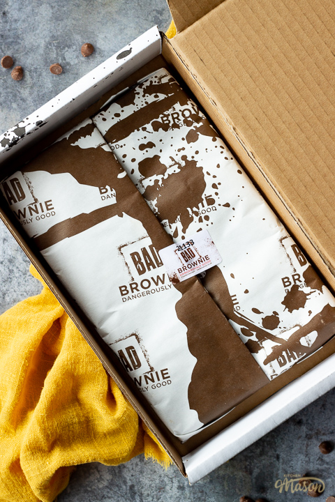 An open but still wrapped box of Bad Brownie brownies on a yellow linen napkin against a grey backdrop with chocolate chips scattered around.