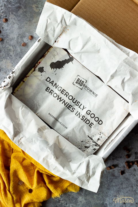 """An open box of Bad Brownie brownies with a sheet saying """"dangerously good brownies inside"""" on a yellow linen napkin against a grey backdrop with chocolate chips scattered around."""