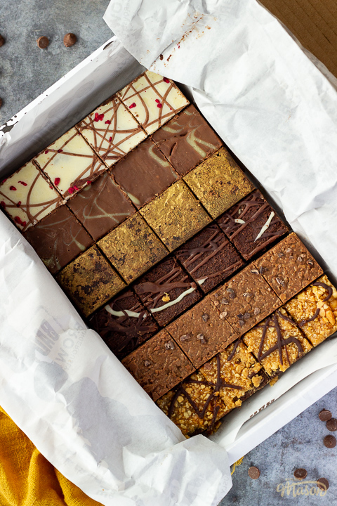 An open box of Bad Brownie brownies revealing all 6 flavours on a yellow linen napkin against a grey backdrop with chocolate chips scattered around.