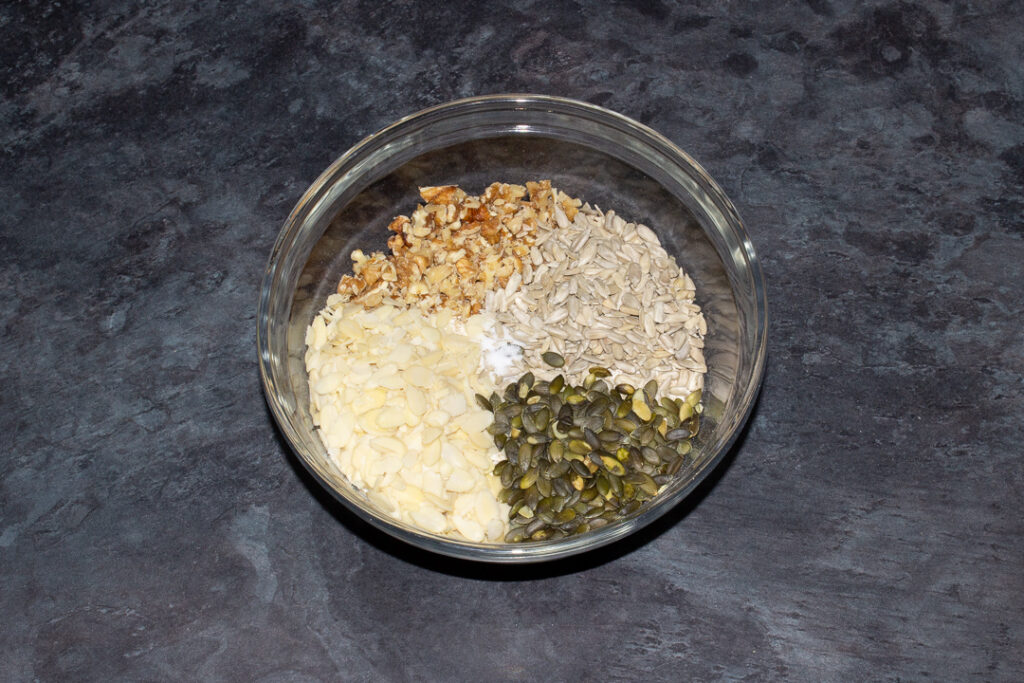 A glass bowl with all the dry homemade granola ingredients in it.