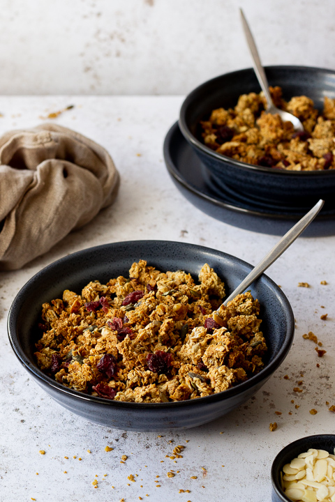 2 blue bowls containing homemade granola and spoons set over light backdrop with granola crumbs scattered everywhere. There is also a small pot with flaked almonds and a light brown napkin in the background.
