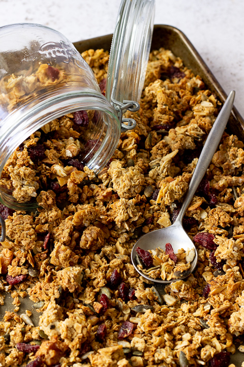 A large baking tray filled with homemade granola set over a light background. There's a glass Kilner jar and a spoon on top.