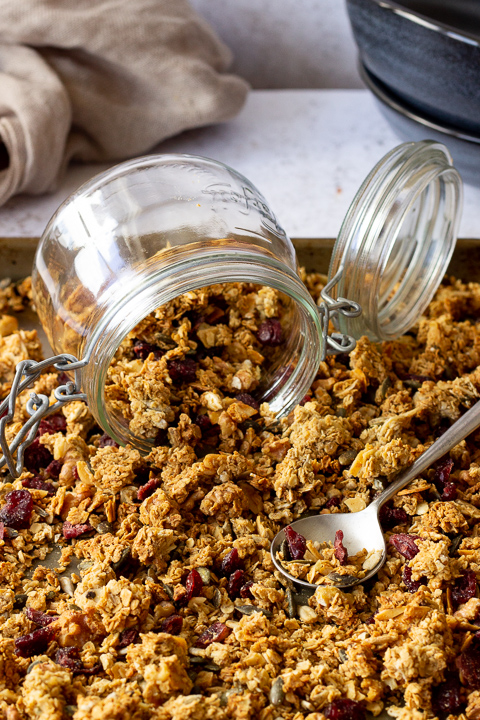 A large baking tray filled with homemade granola set over a light background. There's a glass Kilner jar and a spoon on top plus a light brown napkin and 2 stacked blue bowls in the background.