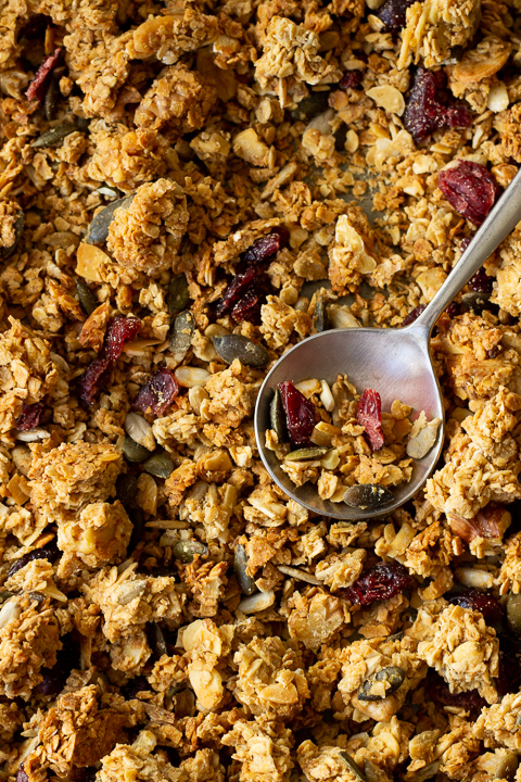 Birds eye view of homemade granola on a baking tray with a spoon on top.