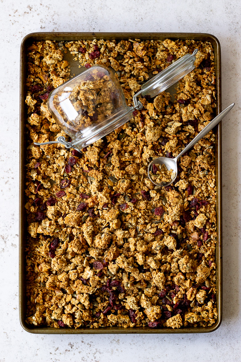 Flat lay view of a tray filled with homemade granola set over a light backdrop. There's also a glass Kilner jar and a spoon in the granola itself.
