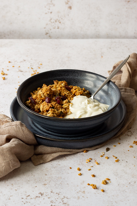 Side view of a blue bowl filled with homemade granola, yoghurt and a spoon set on a blue plate over a light brown napkin. It's set on a light backdrop with granola crumbs scattered around.