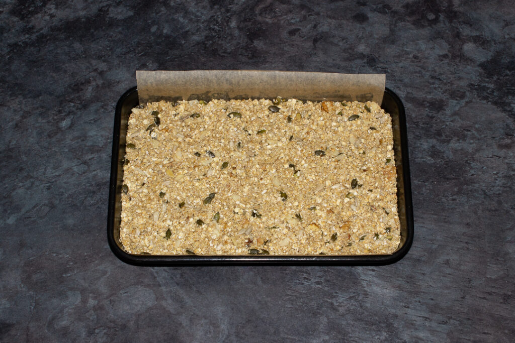 A lined rectangular tin with unbaked homemade granola inside.