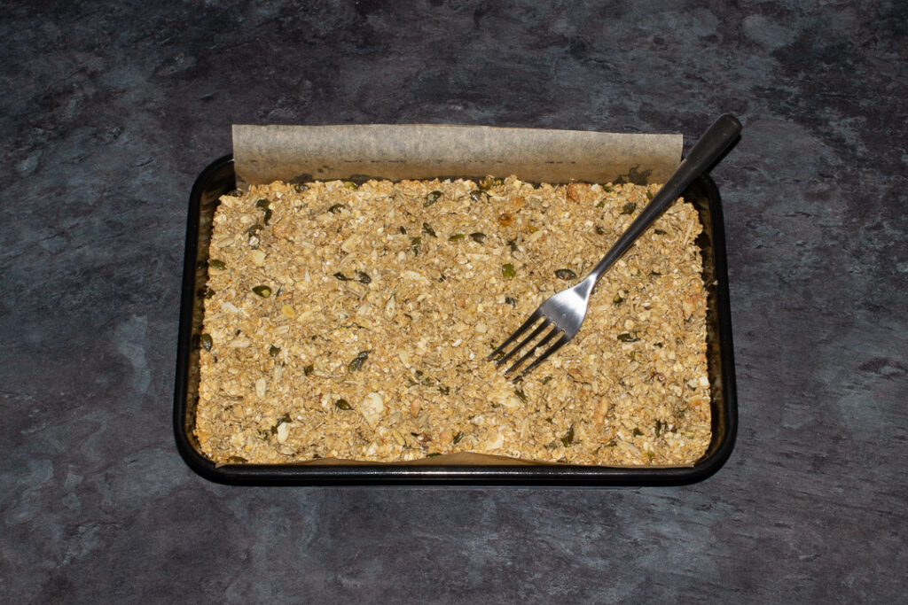 A lined rectangular tin with part baked homemade granola in it and a fork resting on top