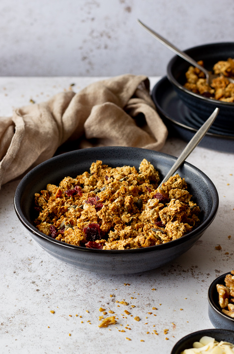 2 blue bowls containing homemade granola and spoons set over light backdrop with granola crumbs scattered everywhere. There are also 2 small pots with walnuts and flaked almonds and a light brown napkin in the background.
