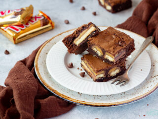 3 Twix brownies and a fork stacked on a white ribbed plate over a mottled grey backdrop. There are 2 Twix bars, a brown linen napkin and chocolate chips scattered in the background.