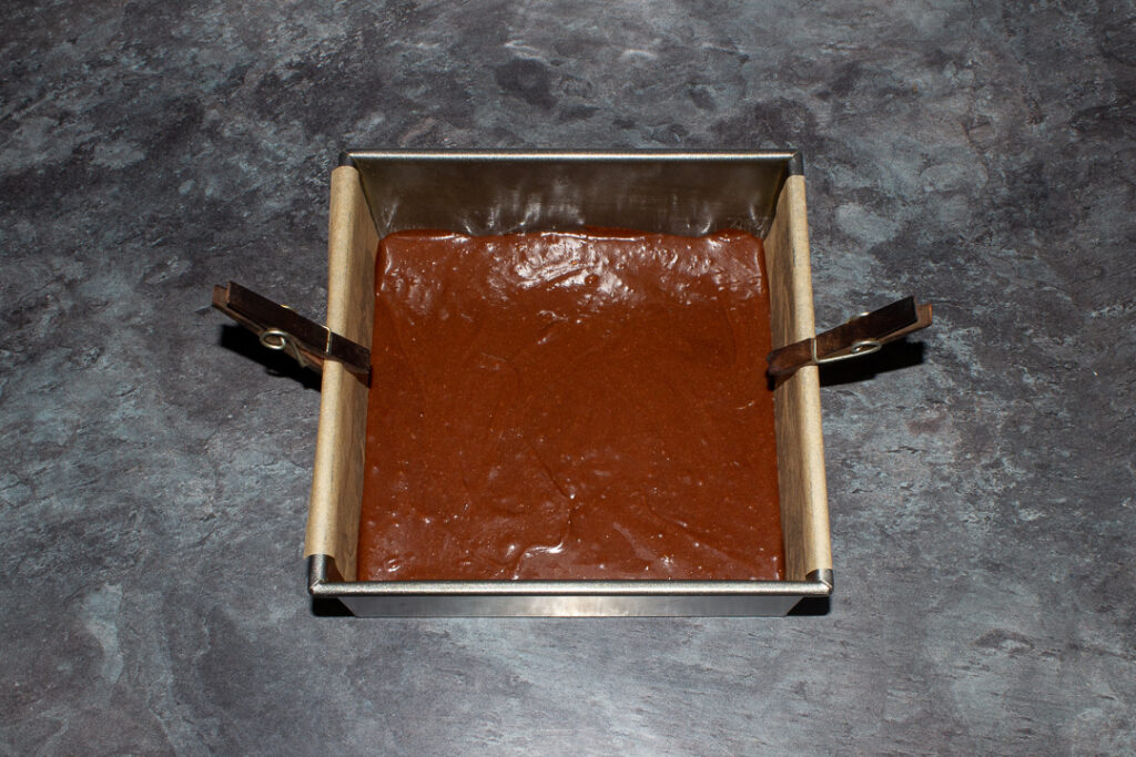 Twix brownie batter in a lined square baking tin.