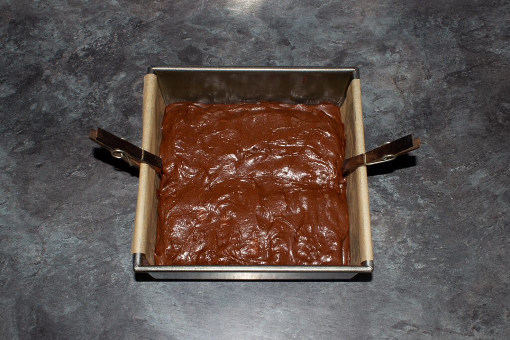 Twix brownies in a lined square baking tin ready to be baked.