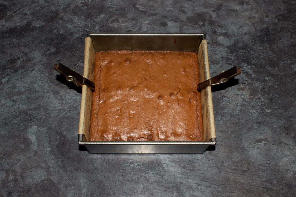 Baked Twix brownie in a lined square baking tin.