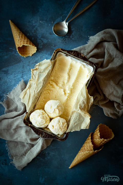 Vanilla ice cream in a lined loaf tin with 3 scoops at the end. Set over a crumpled light brown napkin over a deep blue mottled backdrop. There are 3 waffle cones and a spoon in the background.