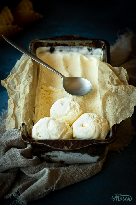 Font view of vanilla ice cream in a lined loaf tin with 3 scoops at the end and a spoon on top. Set over a crumpled light brown napkin over a deep blue mottled backdrop. There are 2 waffle cones in the background.