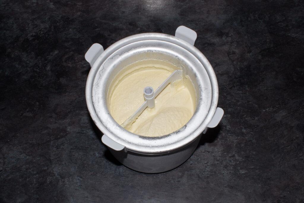 Vanilla ice cream in the bowl of an ice cream churner on a kitchen worktop.