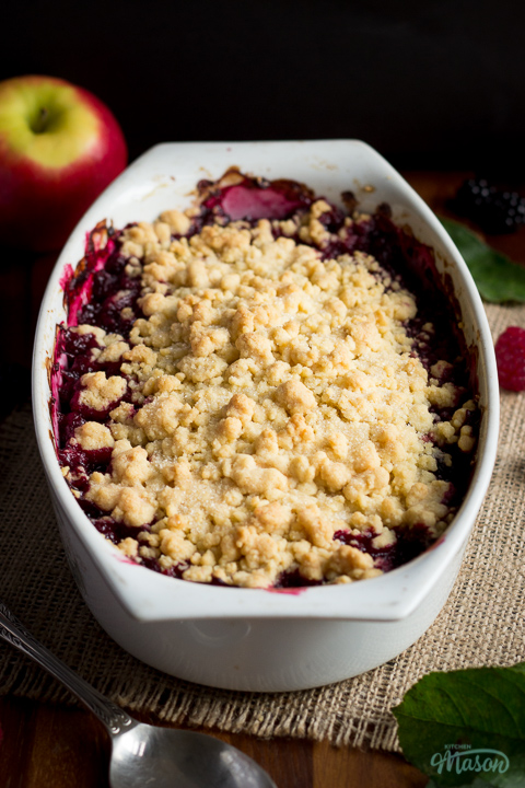 Front angled view of apple berry Summer fruit crumble on a piece of frayed hessian fabric over a wooden worktop. There are berries, leaves an apple and a spoon in the background.